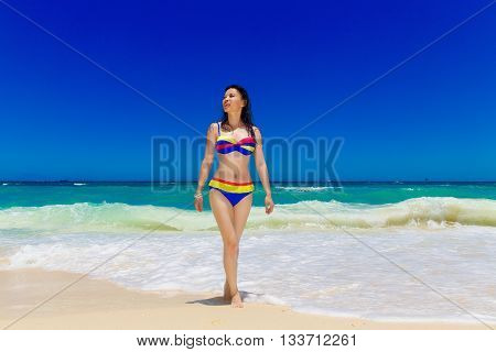 Young beautiful Asian girl with long black hair in bikini on the beach of a tropical island. Summer vacation concept.