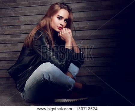 Beautiful Biker Woman Thinking In Black Fashion Jacket And Jeans On Street Wall Background. Dark Por
