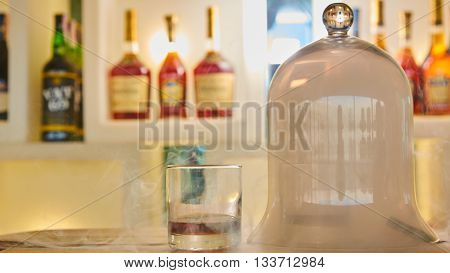 Guatemalan rum under a glass dome with smoke.