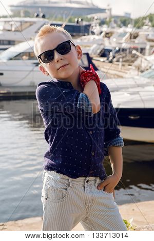 baby boy blond 8 years in a blue shirt, light trousers and sun glasses walking on the promenade by the water with yachts moored near the shore in summer in Sunny weather