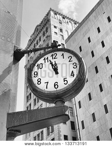 downtown street clock at a few minutes before twelve in black and white