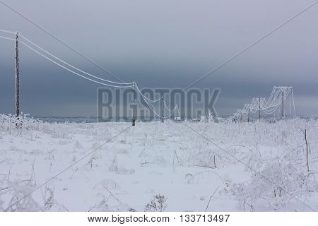 Broken phase electrical power lines with hoarfrost on the wooden electric poles on countryside in the winter pole with wires after storm