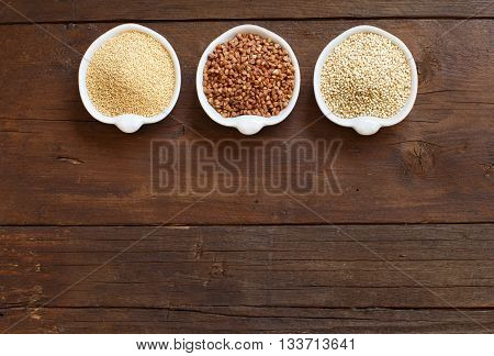 Amaranth buckwheat and quinoa in bowls on a wooden table