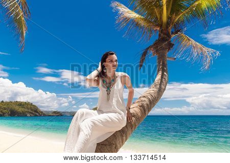 Young beautiful bride in white dress on the palm tree on a tropical beach. Tropical sky and see in the background. Summer vacation concept.