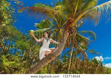 Young beautiful bride with coconut on the palm tree on a tropical beach. Tropical sky in the background. Summer vacation concept.