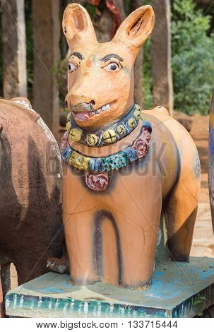 Chettinad India - October 17 2013: Kothamangalam Ayyanar horse shrine. An exception in the line of clay horses this orange clay dog smiles and is attentive.