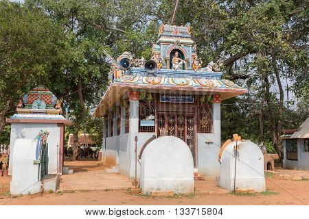 Chettinad India - October 17 2013: Kothamangalam Ayyanar horse shrine. Small Lord Shiva shrine showing him and his two sons Ganesha and Murugan. Ayyanar figures on the corners with nandi the bull.