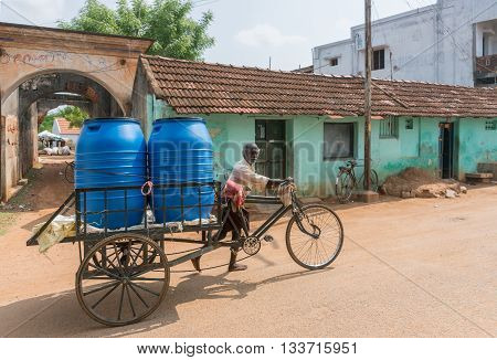 Chettinad India - October 17 2013: Two large blue vats of drinking water on top of bicycle cart pushed by man in street