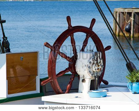 Beautiful traditional wooden ship steering wheel on a sailing boat