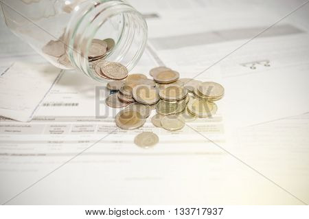 Close up of glass bottle stacking silver coins on paper bill