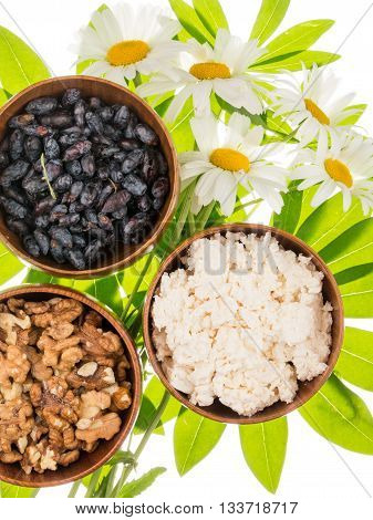 Fresh delicious cottage cheese honeysuckle berries walnuts in brown clay bowl on a background of bright green leaves in the shape of a flower and wild daisies isolated on white background vertical