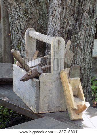 Старый ящик со столярным инструментом. Сад. Скамья.