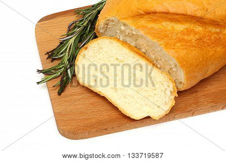 cut crusty tasty bread and green rosemary on a wooden board isolated on a white background
