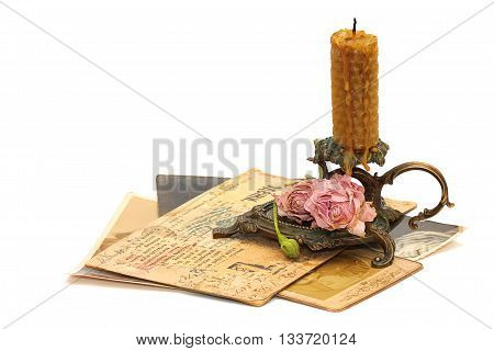 Antique bronze candlestick roses old photos and correspondence isolated on white background