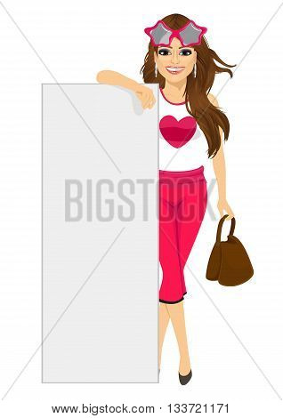 Young fashion woman with handbag leaning on a blank white board