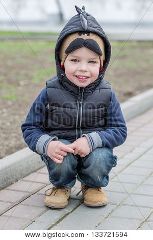 Happy Toddler boy sitting on his haunches outdoors