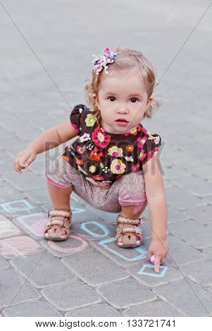 cute little girl drawing with chalk on the pavement