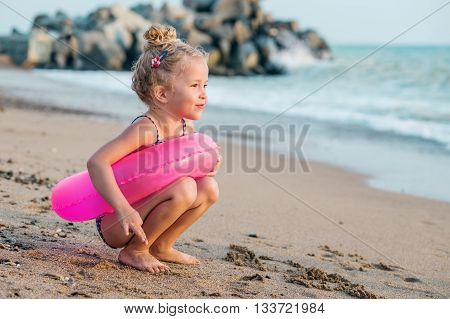 Happy Toddler girl with inflatable circle at sea