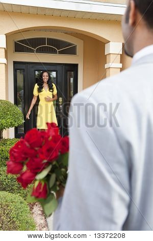 Romantic African American Man Bringing Flowers To Wife Or Girlfriend