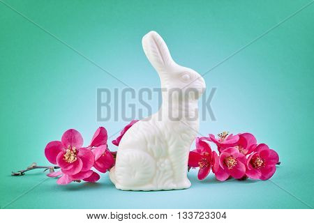white chocolate easter bunny and pink spring flower on green background