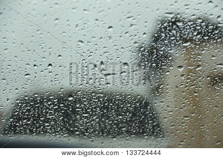 Raindrop on windshield and other car and building with blurred background