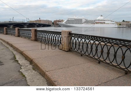 Russia.Saint-Petersburg.The river is lined with granite.On the horizon is a cruise liner.