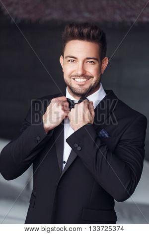 Sexy elegant young caucasian macho man tie a bow