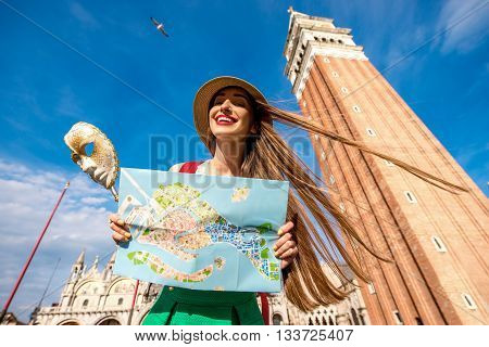 Young smiling woman traveling with carnaval mask and paper map on San Marco square in Venice.