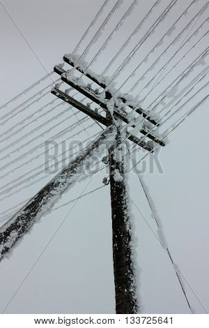 Electrical power lines with hoarfrost on the wooden electric pole on countryside in the winter pole with wires