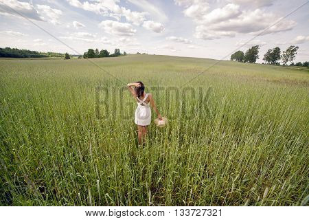 young girl with long dark hair, goes on the green field with tall grass with his face to the camera in a short white dress and straw hat