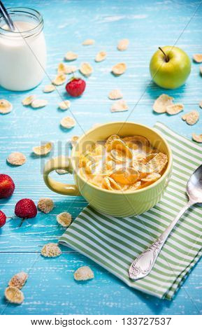 cornflakes with strawberry apple and jar milk on blue wooden table