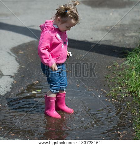 Little girl with funny hairstyle holding paint and brush in rubber boots standing in puddle sunny day outdoor