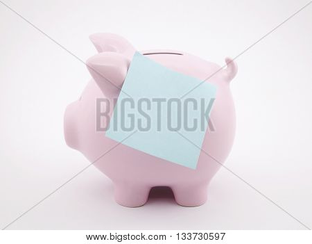 Piggy bank with blank reminder note