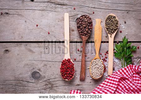 Seasoning for cooking. Red white green and allspice pepper in wooden spoon on aged wooden background. Food ingredient. Selective focus. Flat lay. Place for text.