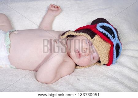 Baby in funny hat asleep peacefully on soft blanket