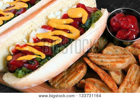 Close Up Of A Hot Dog And Potato Wedges Fully Loaded With Toppings