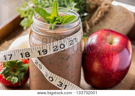 Meal replacement or protein shake with tape measure wrapped around it.