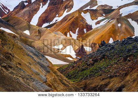 Lonely hiker in colorful rhyolite mountains and fields of lava near Landmannalaugar Iceland