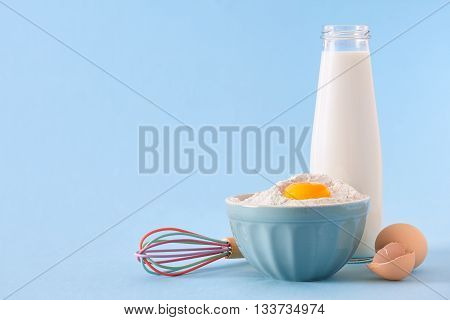 A rural still life with a bottle of milk, domestic eggs, egg whisk and a bowl with flour and yolk on a blue background