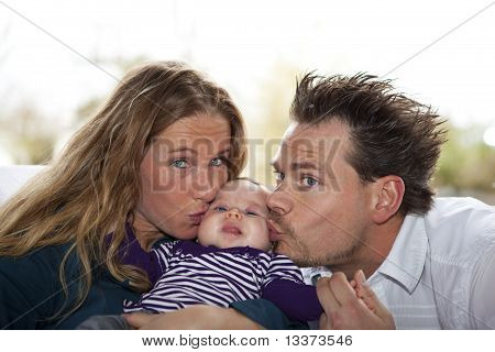 mother and father kissing baby girl