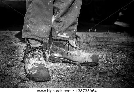 closeup of old and dirty cement worker boots in black and white