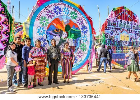 Sumpango Guatemala - November 1 2015: Family pose for photos in front of handmade kites at giant kite festival on All Saints' Day honoring spirits of dead.