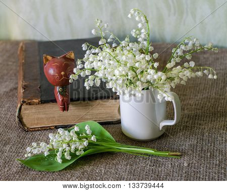 Still life with lily-of-the-valley old book and wooden figure