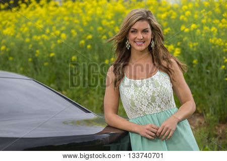 A brunette model posing with a muscle car outdoors