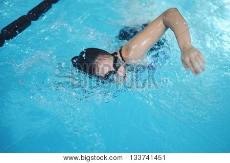 Young woman with goggles swimming at water pool. Indoor.