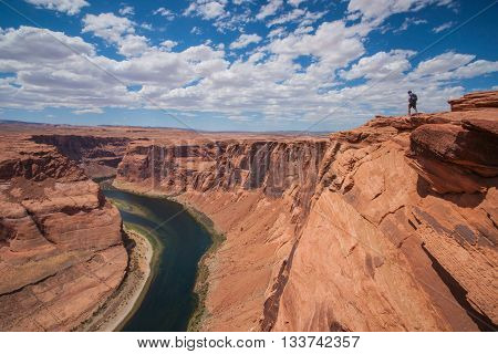 Male hiker walks along the cliff edge of massive Horseshoe Bend in northern Arizona.