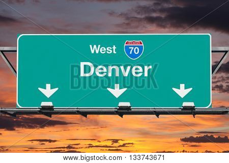 Denver Interstate 70 west highway sign with sunrise sky.