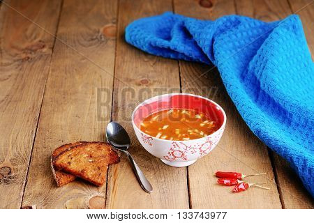 Goulash soup, sliced bread and towel on a table