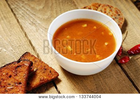 Goulash soup, sliced bread and pepper on a table