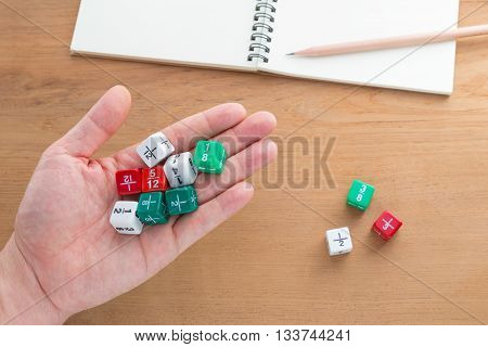Hand holding color fraction dices more fraction dices blank white notebook on wooden desk with copyspace for text selective focus on dices on hand